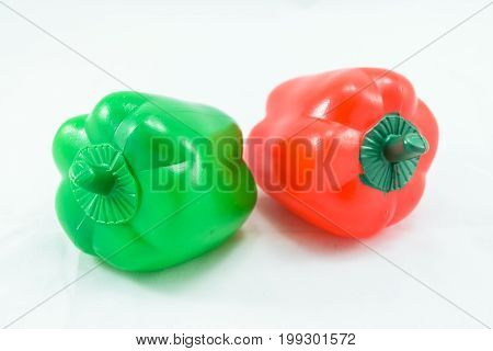 Plastic fake toy red and greeen Bell pepper isolated on white background