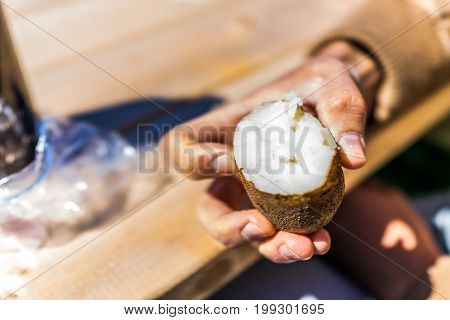 Closeup of cooked russet potato with farmer man holding it at table