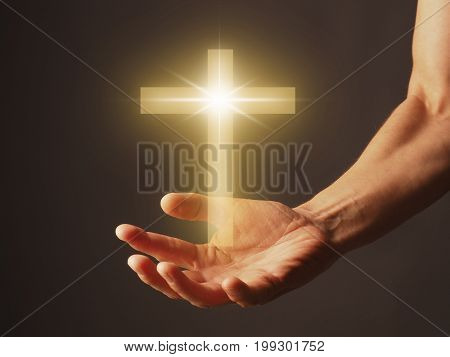 Male hand with a shining cross religion concept image