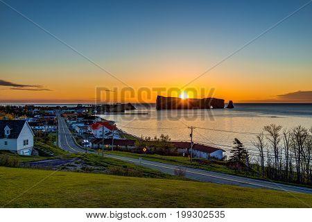 Famous Rocher Perce Rock In Gaspe Peninsula, Quebec, Canada, Gaspesie Region With Cityscape At Sunri