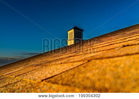 Sunrise With Dark Sky And Illuminated Roof With Chimney Closeup Showing Texture