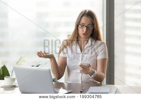 Indignant businesswoman having problem with smartphone, rejecting untimely phone call at workplace, annoyed with discharged or broken cell not working, confused by bad negative news in message