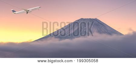 Commercial airplane flying over beautiful natural landscape view of Mount Fuji during sunrise in winter season at Japan. Elegant Design with copy space for travel concept.