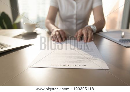 Real estate agent offers to read rental agreement to client for rent house apartment, realtor gives home tenancy document to renter, proposing to sign contract, focus on paper terms, close up