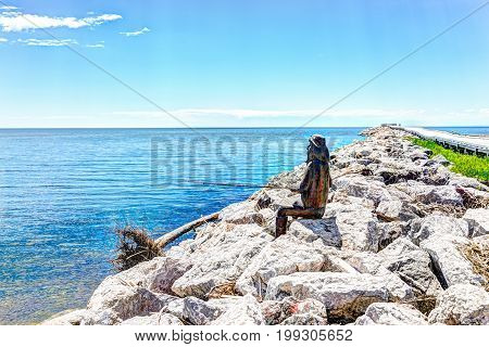 Bonaventure Canada - June 7 2017: Wooden fisherman statue sitting on rocks by pier with pole in summer