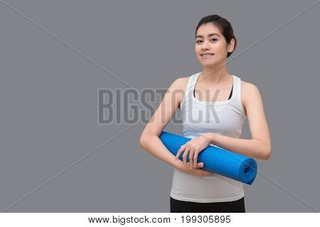 Young Asian Woman Holding Her Yoga Mat At Healthy Sport Gym. Yoga And Meditation Have Good Benefits
