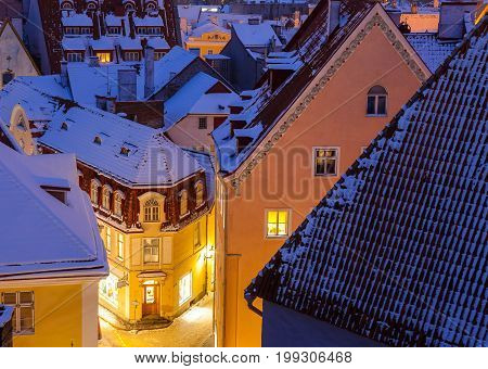 Snowy evening scenic picture of cosy houses and street of Old Town of Tallinn. Winter and Christmas fairy tale of medieval town.