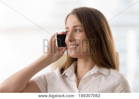 Smiling young businesswoman talking on the phone, happy woman holding cellphone making answering call in roaming, having pleasant private business mobile conversation, stay in touch, head shot