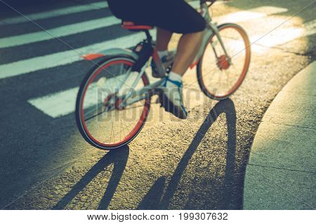 low section of man riding a bike crossing zebra crossing,China.