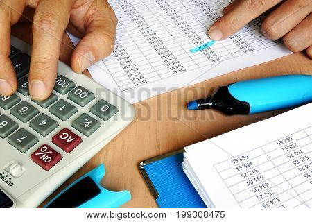 Bookkeeper using calculator to check the figures on the business report. Accounting and audit concept.