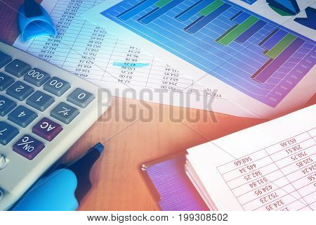 Bookkeeping concept. Calculator and financial figures on an office table.