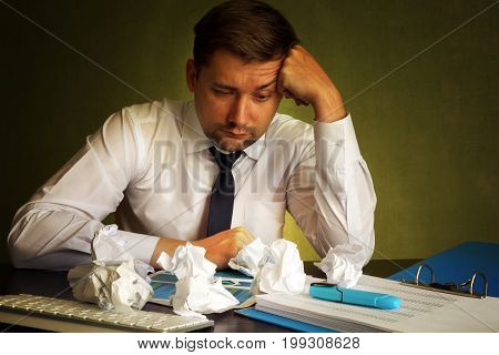 Frustrated businessman looking on a financial report and crumpled paper.