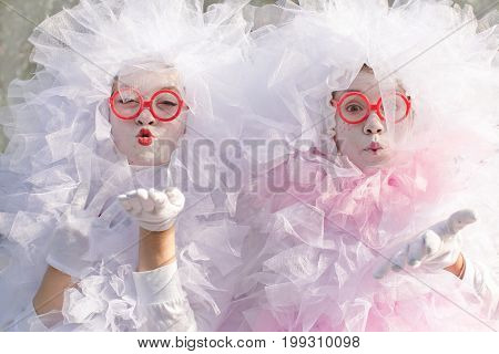 Cheerful festive people with white powder makeup sending air kiss and looking at camera.