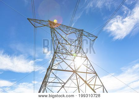 Power lines with the sun coming down and the blue sky above. Shot from the perspective of looking up from below