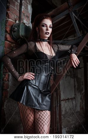 Portrait of the gorgeous goth (deathrock) girl dressed in leaky blouse skirt and bra standing among industrial ruins