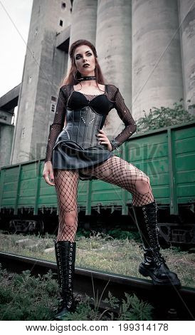 Portrait of the beautiful goth (deathrock) girl dressed in holey blouse skirt corset bra and boots standing in industrial place (factory and railroad)