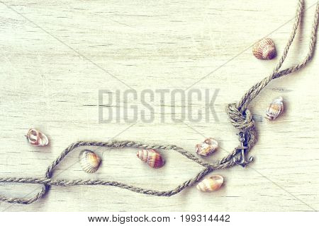 Marine composition background anchor seashell and old rope with knot on a wooden table vacation concept toned