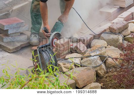Man cutting stone slabs concrete slab with an electric grinder