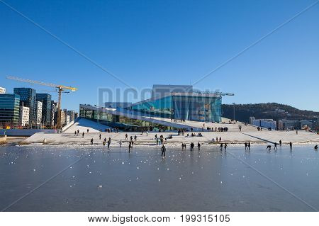 OSLO, NORWAY - 27 FEB 2016: Oslo Opera house with walking and relaxing people at sunny winter day