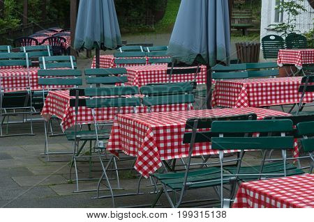Empty beer tables with red white tablecloth and green wooden chairs in a public beer garden.