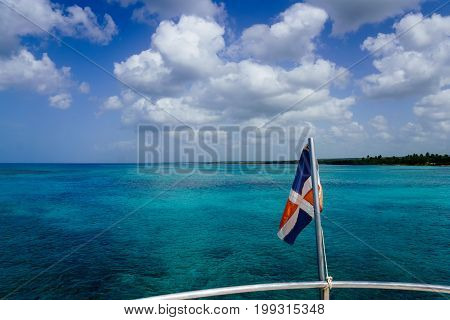Dominican flag over the ocean with cloudy blue sky