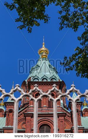 Uspenski Cathedral and fence At Summer Sunny Day. Red Church - Tourist destination In Finnish Capital poster