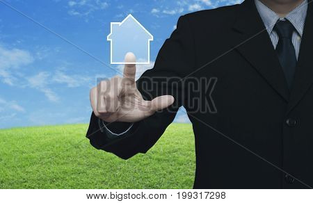 Businessman pressing house icon with copy space over modern city tower street and expressway Real estate concept