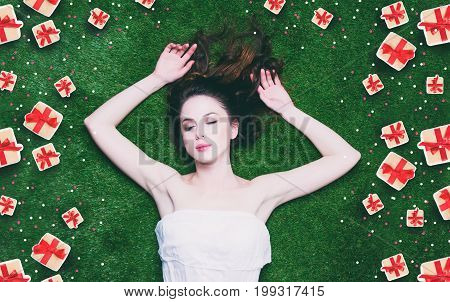 Portrait of a young redhead woman lying down on green spring grass above point of view
