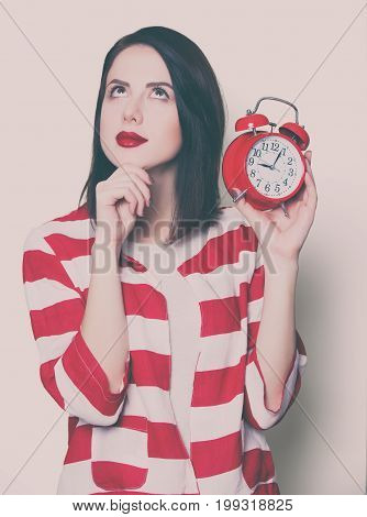 Brown hair girl with alarm clock on white background