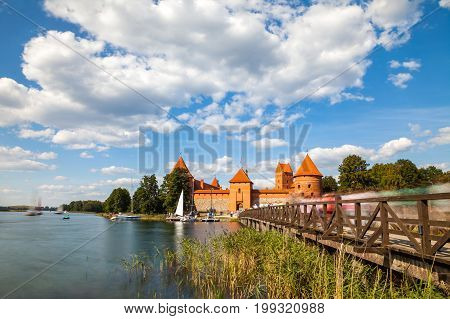 Tourists visit Trakai castle in sunny siummer day, nice time to have boat trip. Long exposure, motion blur