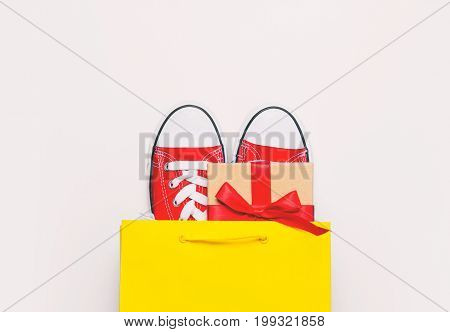 big red gumshoes and beautiful gift in cool shopping bag on the wonderful white background poster