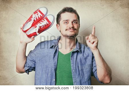 Handsome Young Man Holding Red Gumshoes