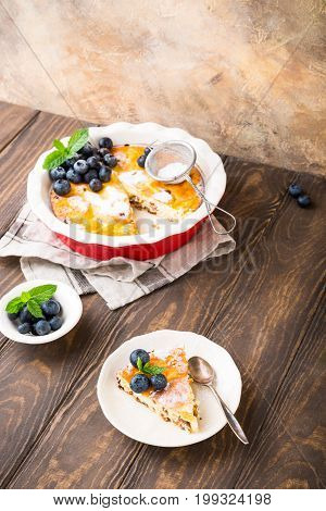 Piece of homemade gluten free cheesecake made from cottage cheese, decorated with blueberries and mint on wooden background. Healthy food concept with copy space.