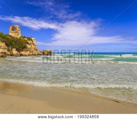 The most beautiful coast of Apulia: Torre Dell'Orso Bay, ITALY (Lecce).Typical seascape of Salento: view of the wide sandy beach of fine silver, the dune with pinewood, and old ruin of watchtower.