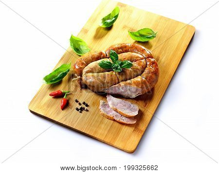 Close up view of roasted traditional homemade sausage with spices and herbs and spices spicy meat baked with herbs and spice on wooden cutting board.