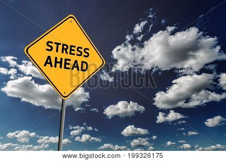Background of dark blue sky with cumulus clouds and yellow road sign with text Stress Ahead