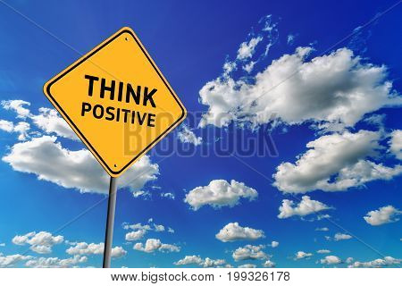 Background of blue sky with cumulus clouds and yellow road sign with text Think Positive