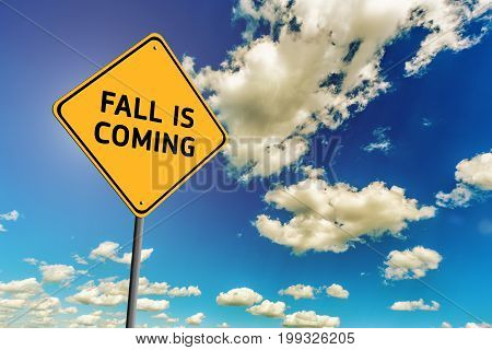 Background of blue sky with cumulus clouds and yellow road sign with text Fall is Coming