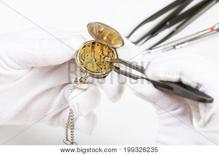 Adjusting Of Old Pocket Watch By Tweezers