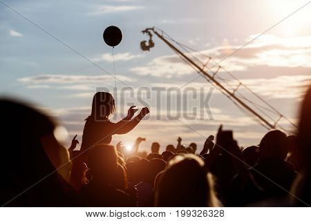 Silhouette of girl at Outdoors Music Festival at sunset
