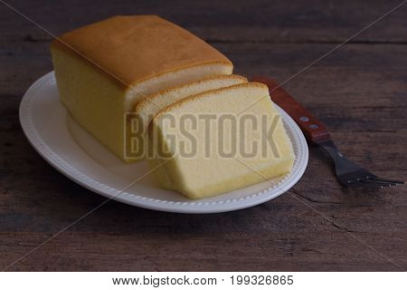 Slices of butter cake on white plate. Homemade plain butter cake so delicious soft and moist. Tasty pound cake or butter cake ready to served on rustic wood table. Homemade bakery concept with copy space for background or wallpaper.