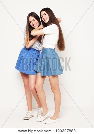 Full body portrait of two happy  girls wearing blue skirts over white background