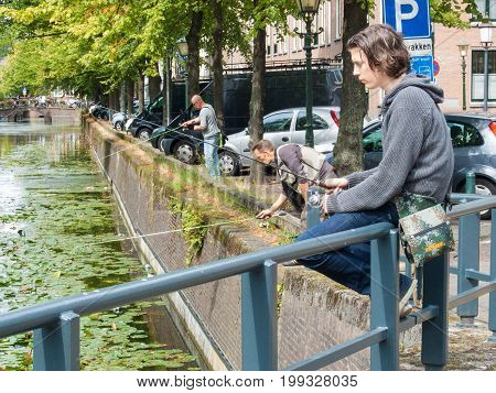 The Hague the Netherlands - 1 July 2017: Young man fishing on canal during urban fishing competition