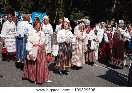 TALLINN, ESTONIA - 04 JUL 2014: Aged women Estonian costumes preparing to ceremonial procession of Estonian song and dance festival