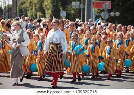 TALLINN, ESTONIA - 04 JUL 2014: Children in Estonian costumes going at ceremonial procession of Estonian song and dance festival