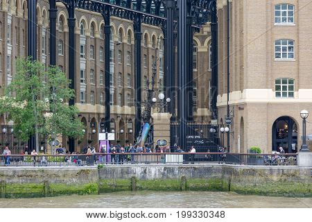 LONDON ENGLAND - JUNE 08 2017: Renovated old buildings with people at South Bank river Thames in London England
