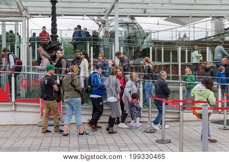 LONDON ENGLAND - JUNE 08 2017: Tourists in waiting queue for visiting London Eye in London England