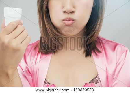 Woman rinsing and gargling while using mouthwash from a glass During daily oral hygiene routine Girl in a pink silk nightwear Dental Healthcare Concepts