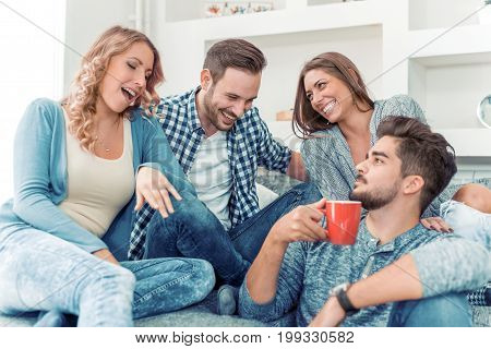Young friends having a great time in living room.Group of young people sitting and smiling with coffee.