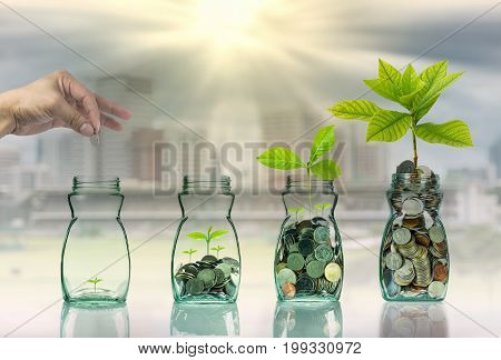 Hand putting mix coins and seed in clear bottle on cityscape photo blurred cityscape backgroundBusiness investment growth concept,3D illustration